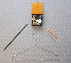 Matériel pour un sistre: un cintre en métal, du fil métallique, un bâtonnet en bois, des boutons