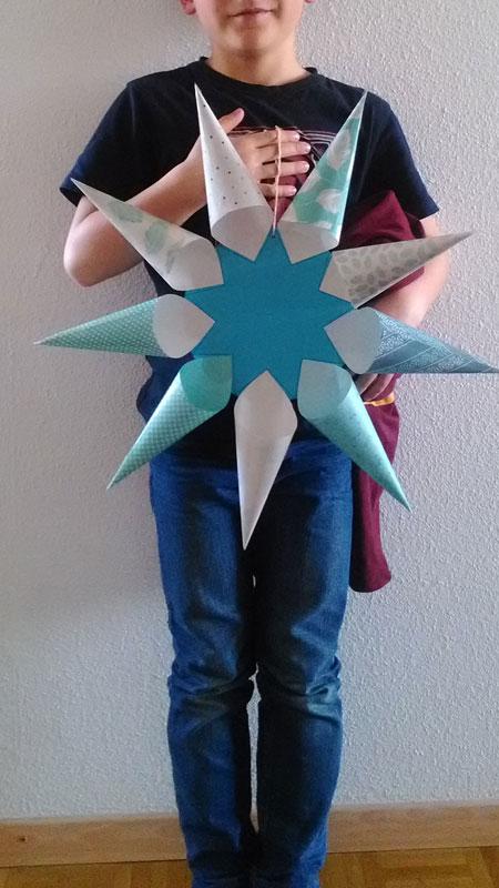 Un petit garçon qui l'étoile qu'il a réalisée et qui pose fièrement devant l'objectif :)